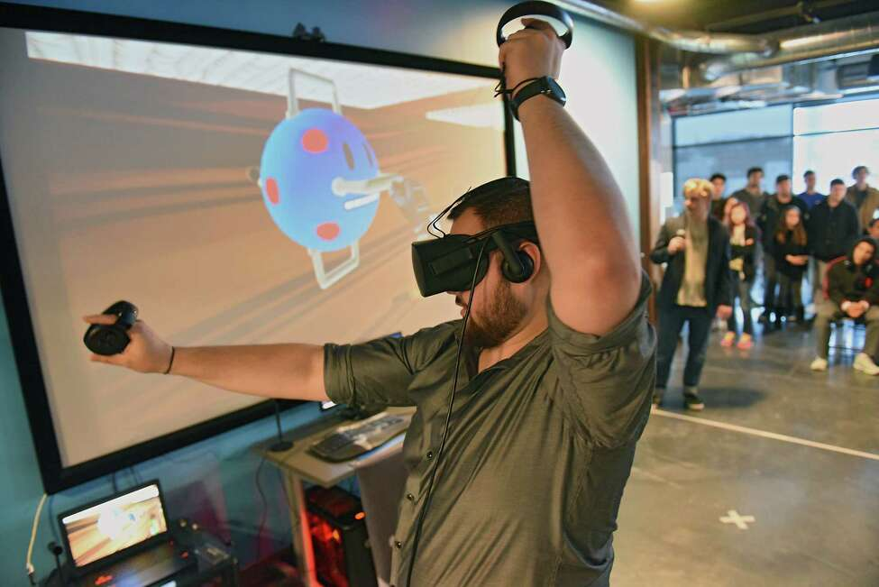 Connor Thomas of Gaming Insomniacs demonstrates virtual reality game Don't Look Down as Catapult Games releases the new game during a Catapult Launch Party at Urban Co-Works on Thursday, April 18, 2019 in Schenectady, N.Y. Don't Look Down is a fully immersive virtual reality game that has players climbing and flinging through four distinct settings while battling robots.(Lori Van Buren/Times Union)