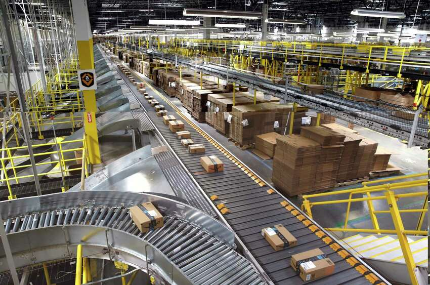 FILE- In this Aug. 3, 2017, file photo, packages ride on a conveyor system at an Amazon fulfillment center in Baltimore. Outside of ditching online shopping altogether, there are some small tweaks in how you shop that can cut down on the impact on the environment, such as slowing down shipping times and not filling up the cart with stuff you know you won?t keep. (AP Photo/Patrick Semansky, File)