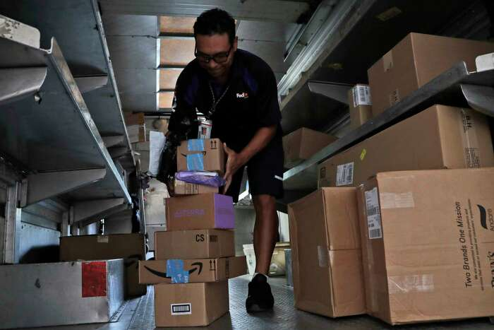 FILE - In this July 17, 2018, file photo, a FedEx employee delivers packages in Miami. Outside of ditching online shopping altogether, there are some small tweaks in how you shop that can cut down on the impact on the environment, such as slowing down shipping times and not filling up the cart with stuff you know you won?t keep. (AP Photo/Lynne Sladky, File)