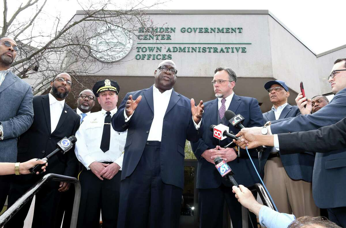 Rev. Boise Kimber (center) flanked by Hamden Acting Police Chief John Cappiello (left) and Hamden Mayor Curt Leng (right) addresses the media outside of the Hamden Government Center on April 19, 2019 after a meeting between the town officials and local clergy concerning the recent shooting by a Hamden police officer.