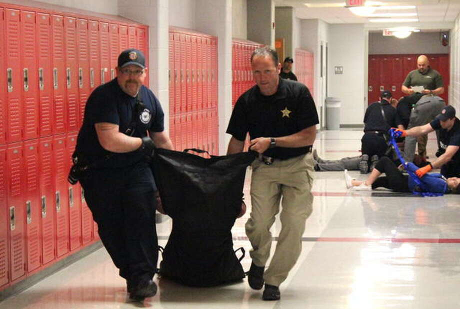 Emergency responders practice carrying victims out of an active shooter situation during training Friday at Alton High School. The Madison County Sheriff's Department and Godfrey Fire Protection District teamed up for the training, which emphasized teams for firefighters, EMS and police officers responding to the incident. Photo: Steven Spencer | The Telegraph