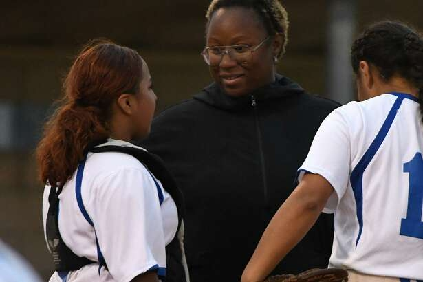 Dekaney Head Softball Coach ?????????????, center, pumps up her battery of catcher Alexa Villa, left, and ???????? in the top of the 4th inning of their District 16-6A matchup at Dekaney High School on April 12, 2019.
