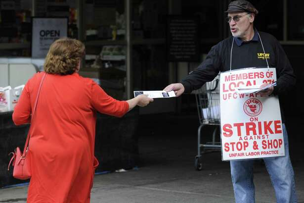 Terry McCaffrey of Stamford, Union Shop Stewart for Local #371, passes out a flyer to a customer of Stop & Shop as union employees walk the strike line Thursday, April 19, 2019 at one of the Stamford, Conn. stores.