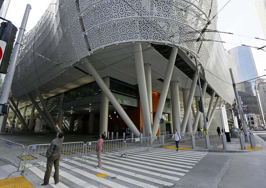 FILE - In this Sept. 27, 2018, file photo, people stop to look at the closed Salesforce Transit Center in San Francisco. Officials say the $2 billion transit terminal in San Francisco that shut down six weeks after opening last year is on track to be repaired by June, 2019, but there is no firm re-opening date. The Transbay Joint Powers Authority operates the Salesforce Transit Center, which opened Aug. 12, 2018 to great fanfare. They closed it the following month after finding two cracked beams. (AP Photo/Eric Risberg, File) Photo: Eric Risberg, Associated Press