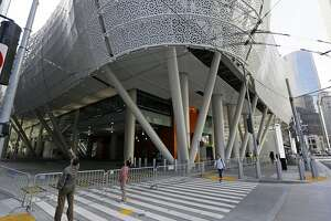 FILE - In this Sept. 27, 2018, file photo, people stop to look at the closed Salesforce Transit Center in San Francisco. Officials say the $2 billion transit terminal in San Francisco that shut down six weeks after opening last year is on track to be repaired by June, 2019, but there is no firm re-opening date. The Transbay Joint Powers Authority operates the Salesforce Transit Center, which opened Aug. 12, 2018 to great fanfare. They closed it the following month after finding two cracked beams. (AP Photo/Eric Risberg, File)