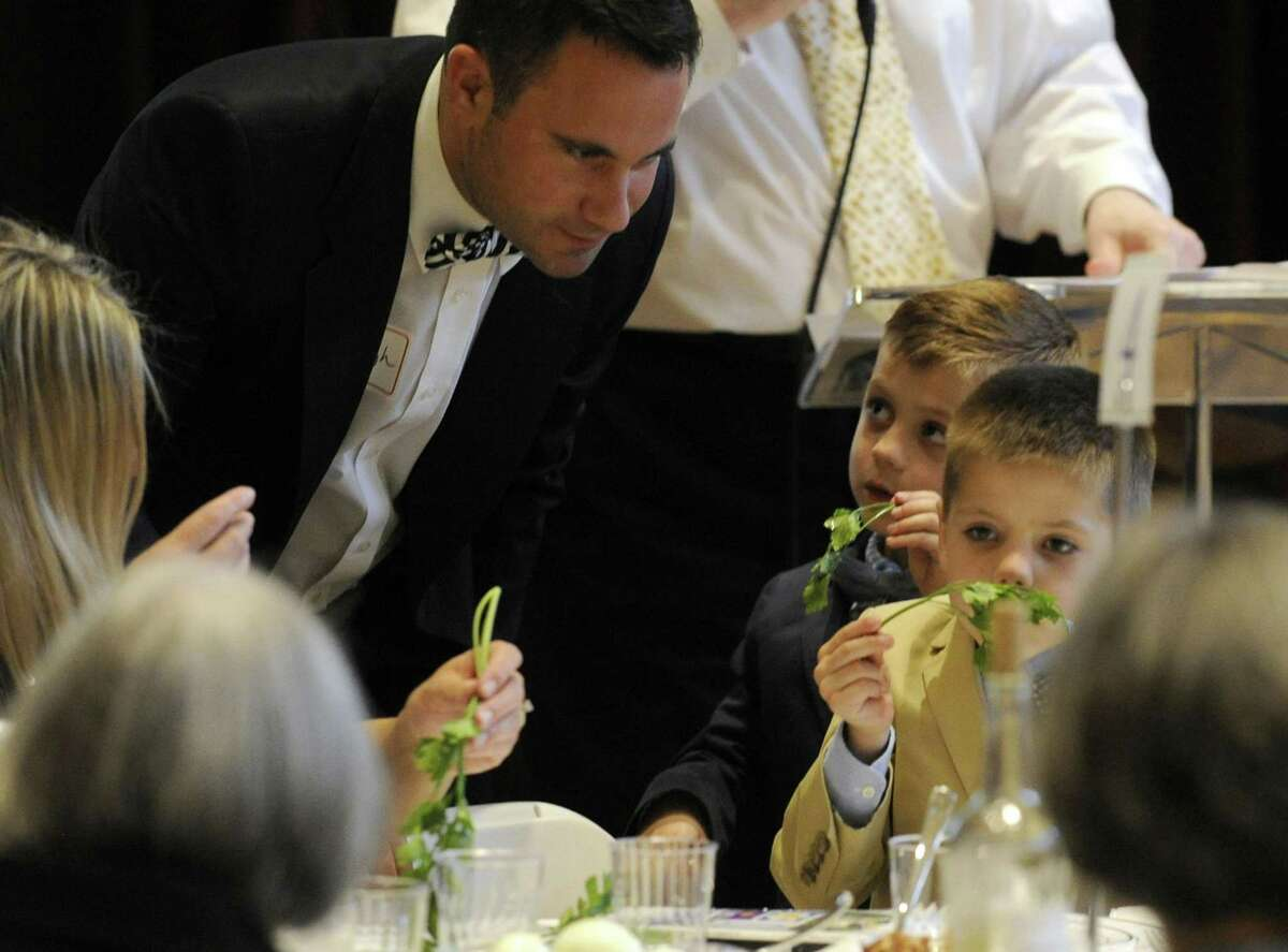Rev. Daniel Haugh, Associate Pastor of Round Hill Community Church, watches as his sons Jack and Blake smell and taste parsley dipped in saltwater during an Interfaith Passover Seder at Temple Sholom on Friday in Greenwich. Parsley is a symbol of spring, and saltwater signifies tears the Israelites slaves shed. The Passover Seder is a Jewish ritual feast that marks the beginning of the Jewish holiday of Passover.