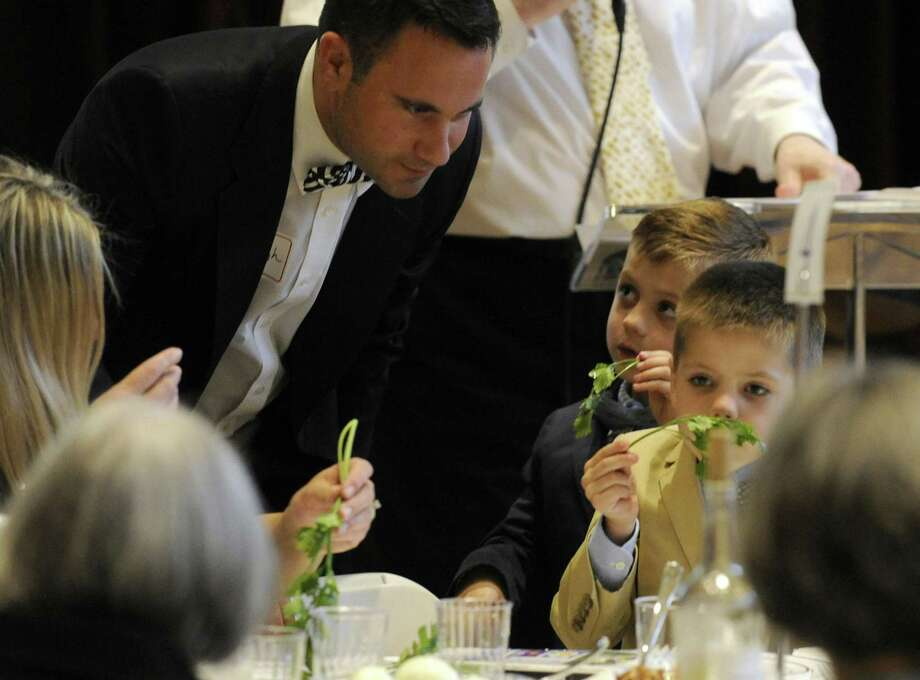 Rev. Daniel Haugh, Associate Pastor of Round Hill Community Church, watches as his sons Jack and Blake smell and taste parsley dipped in saltwater during an Interfaith Passover Seder at Temple Sholom on Friday in Greenwich. Parsley is a symbol of spring, and saltwater signifies tears the Israelites slaves shed. The Passover Seder is a Jewish ritual feast that marks the beginning of the Jewish holiday of Passover. Photo: Matthew Brown / Hearst Connecticut Media / Stamford Advocate