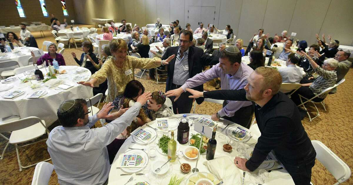 Members of Martin Diamond family hold their hands over children as they are blessed during an Interfaith Passover Seder at Temple Sholom on Friday, April 19, 2019 in Greenwich, Connecticut. The Passover Seder is a Jewish ritual feast that marks the beginning of the Jewish holiday of Passover. The Diamonds are from Greenwich.