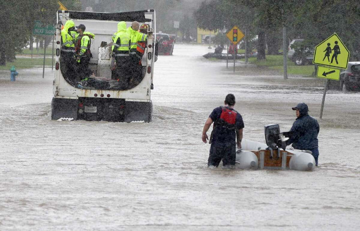 A rescue truck and a boat move along Edgebrook on Sunday, Aug. 27, 2017, after Hurricane Harvey rains flooded much of the area.