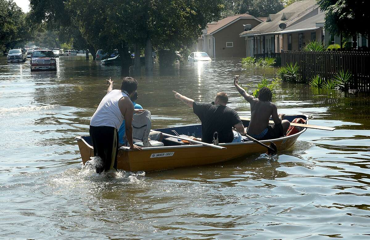 Port Arthur residents wave to neighbors Thursday, Aug. 31, 2017, as they make their way by boat through their flooded roadways after Hurricane Harvey.