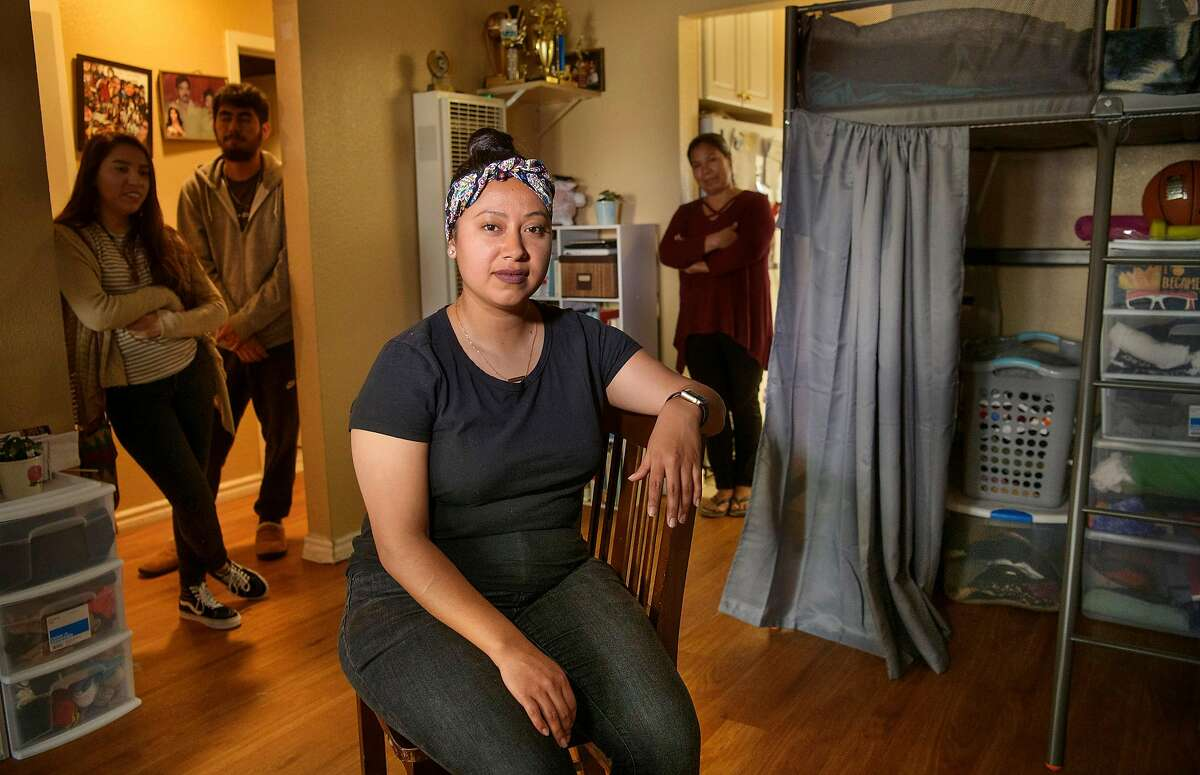 Teacher Roxana De La O Cortez, center, at her home in Hayward, Calif., Saturday, Mar. 2, 2019. Behind her are her sister Odalis De La O Cortez, left, brother Manual De La O Cortez, and their mother Antonia Cortez Garcia who all live together in the apartment.