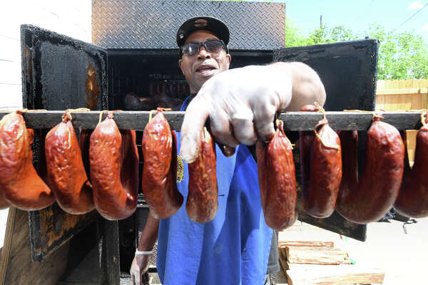 Charles Brewer holds a rack of links at his barbecue restaurant in Beaumont Friday. Brewer's place Charlie's has been recognized by Texas Monthly and is on the magazine's midterm list of best barbecue in Texas. Photo taken Friday, 4/19/19