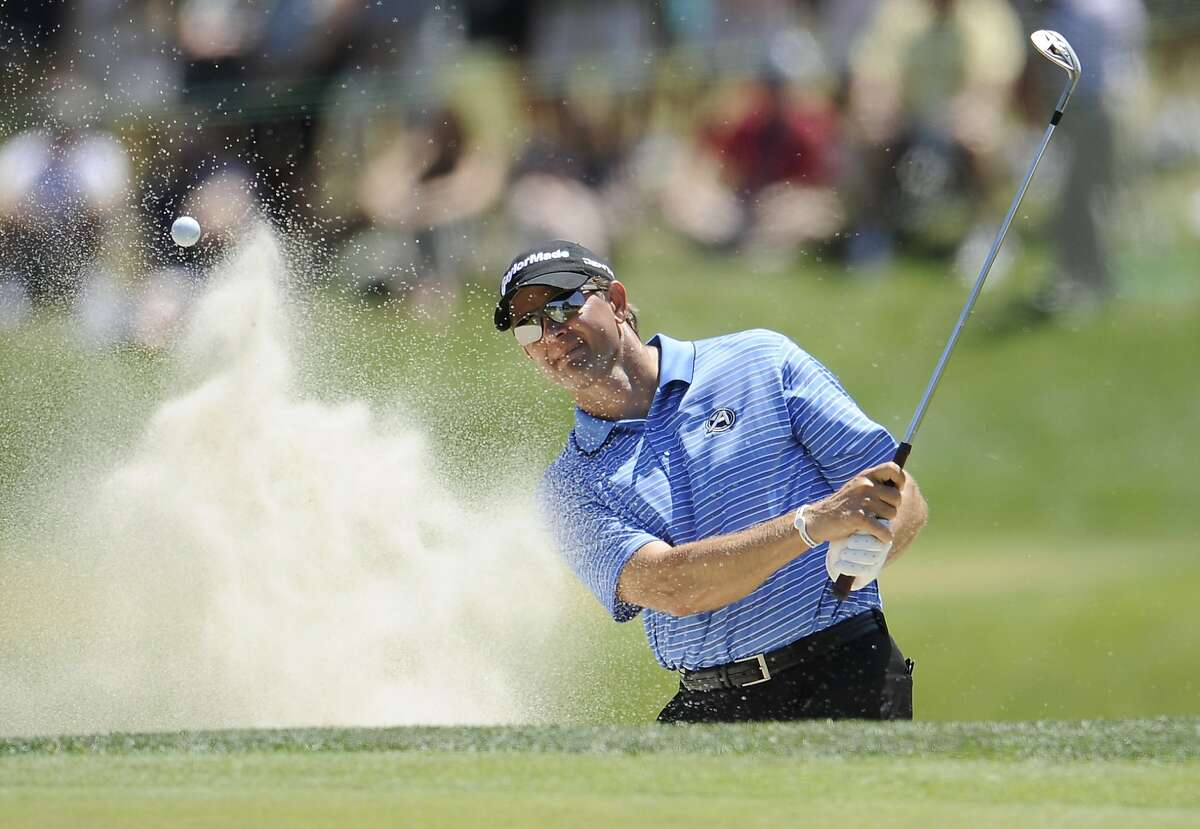 Retief Goosen, of South Africa, blasts from a bunker to the 18th green during a practice round for the U.S. Open Championship golf tournament in Bethesda, Md., Wednesday, June 15, 2011. (AP Photo/Nick Wass)