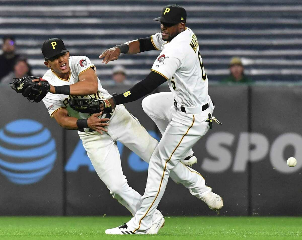 Pittsburgh Pirates shortstop Erik Gonzalez, left, and center fielder Starling Marte collide going for a ball hit by San Francisco Giants' Yangervis Solarte during the eighth inning of a baseball game Friday, April 19, 2019, in Pittsburgh. (Matt Freed/Pittsburgh Post-Gazette via AP)