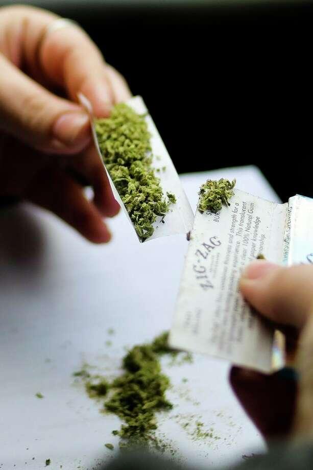 Midland resident Samatha Creech rolls marijuana before smoking on Friday afternoon. (Katy Kildee/kkildee@mdn.net)