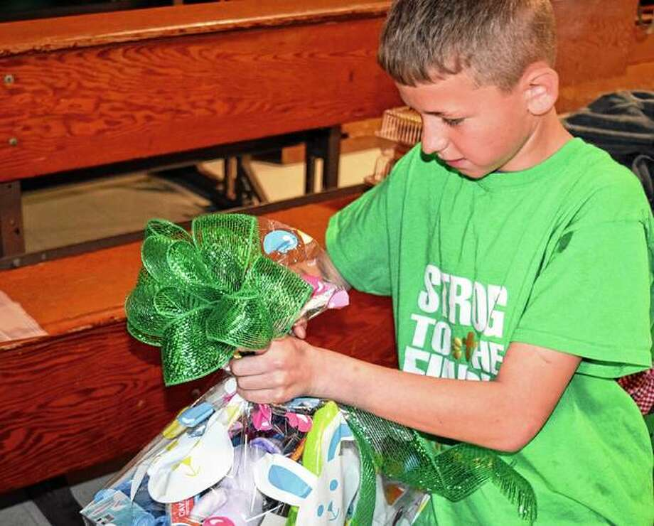 Seventh-grader Jacob Kollman ties a ribbon on an Easter basket Friday in preparation for a day of good deeds in honor of Good Friday.
