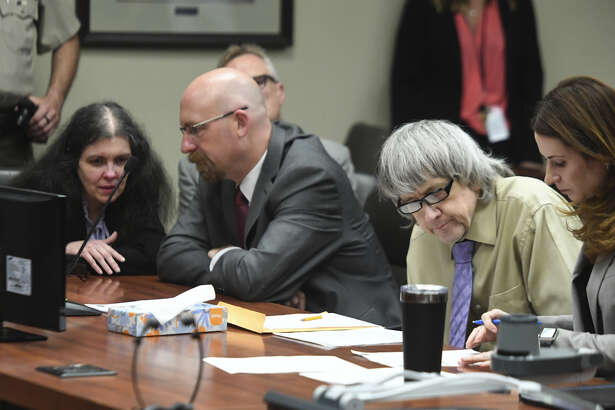 David Turpin, second from right, and wife, Louise, left, sit in a courtroom during their sentencing hearing Friday, in Riverside, Calif. The California couple who pleaded guilty to years of torture and abuse of 12 of their 13 children have been sentenced to life in prison with possibility of parole after 25 years.