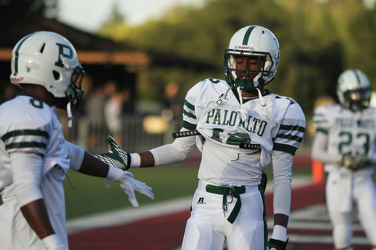 Palo Alto Football players Keesean Johnson, right, greets Malcom Davis during a warm up at Foothill College in Los Altos, Calif. on Saturday, Sept. 21, 2013. The Mitty Monarchs took on Palo Alto High School at Foothill College.