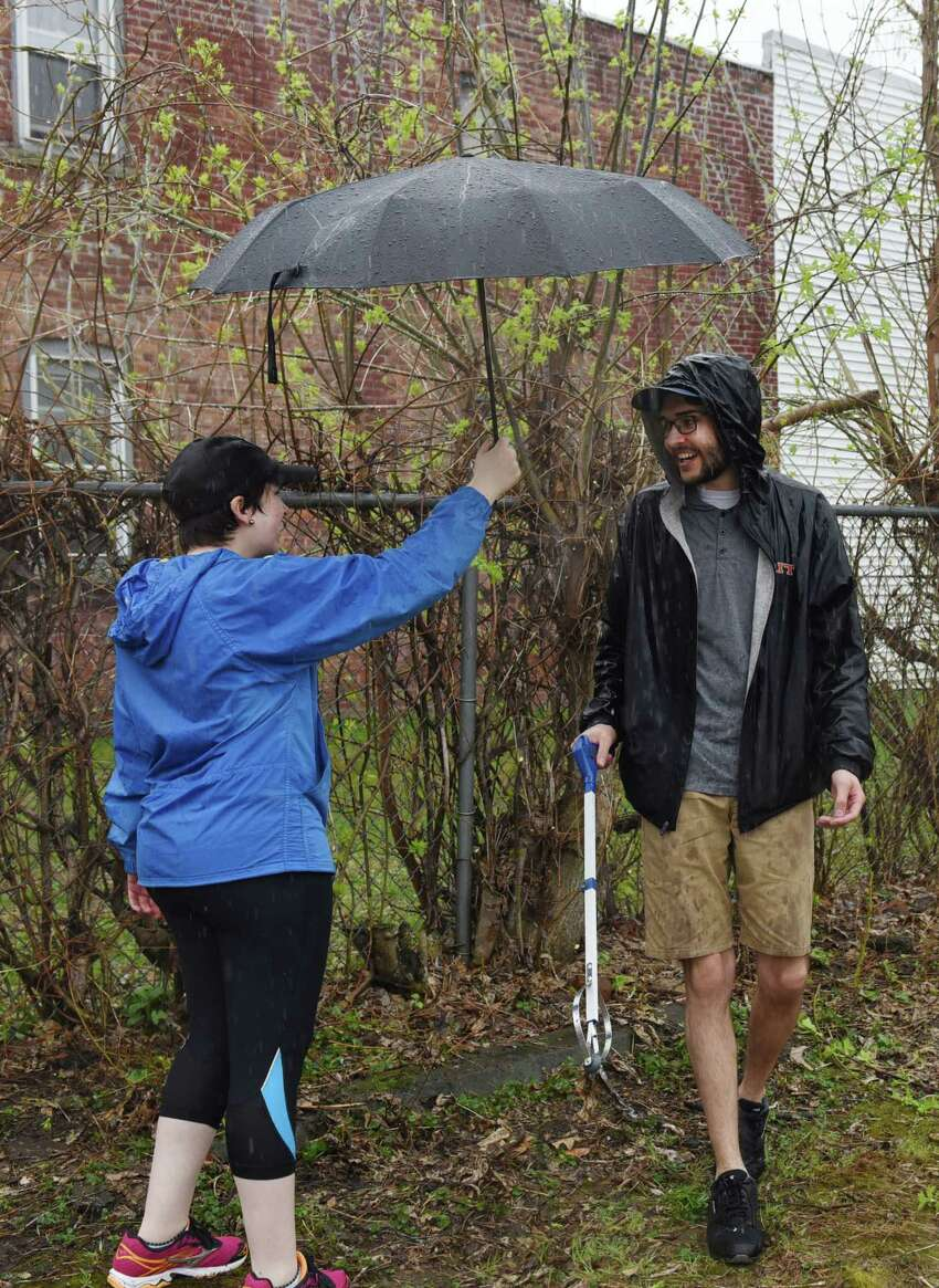 Holly McMahon holds up an umbrella while her and Dana Wright clean up trash in the rain on Saturday, April 20, 2019 at the Lots of Hope site in Troy, NY. (Phoebe Sheehan/Times Union)