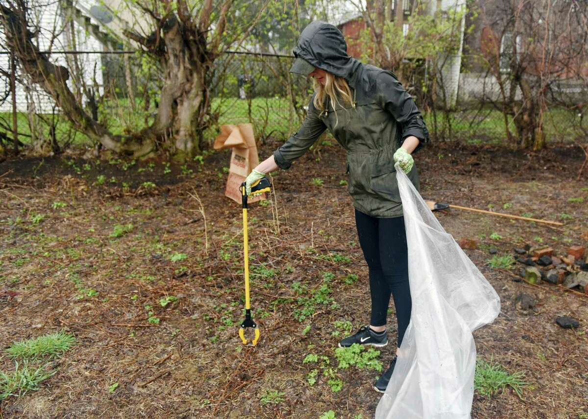 Amy Pamkowski cleans up garbage and debris in the rain on Saturday, April 20, 2019 at the Lots of Hope site in Troy, NY. (Phoebe Sheehan/Times Union)