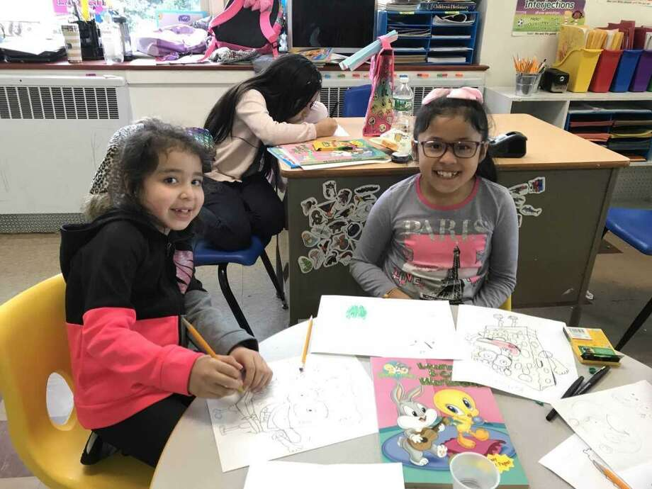 """In the Family First in Education classroom, Kaylee Son, Danna Dias and Katherine Cojitambo practice their cartooning skills. The elementary school artists use materials such as crayons, pens, and books provided by National Cartoonists Society Connecticut Chapter, supplied to Family First during their visit to """"Masterpieces from the Museum of Cartoon Art"""" at Bruce Museum. Photo: Contributed"""