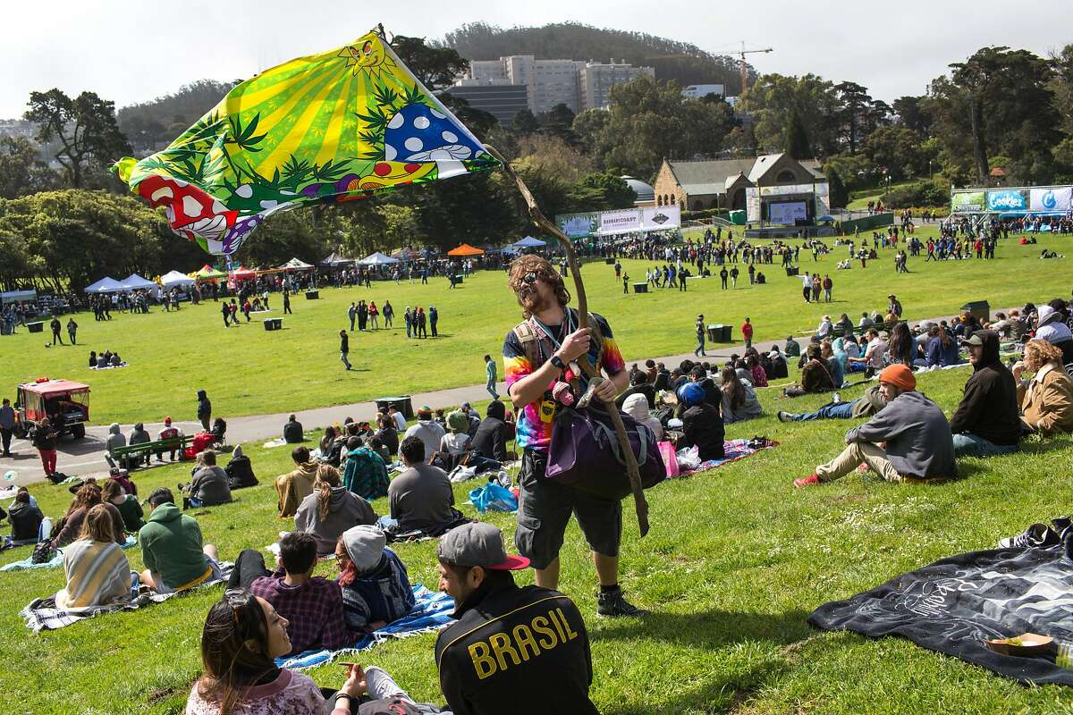 Kelly Jensen holds a flag while he makes his way through the crowd offering goods for sale during the annual 420 in the Park pot festival at Hippie Hill in Golden Gate Park. Saturday, April 20, 2019. San Francisco, Calif.