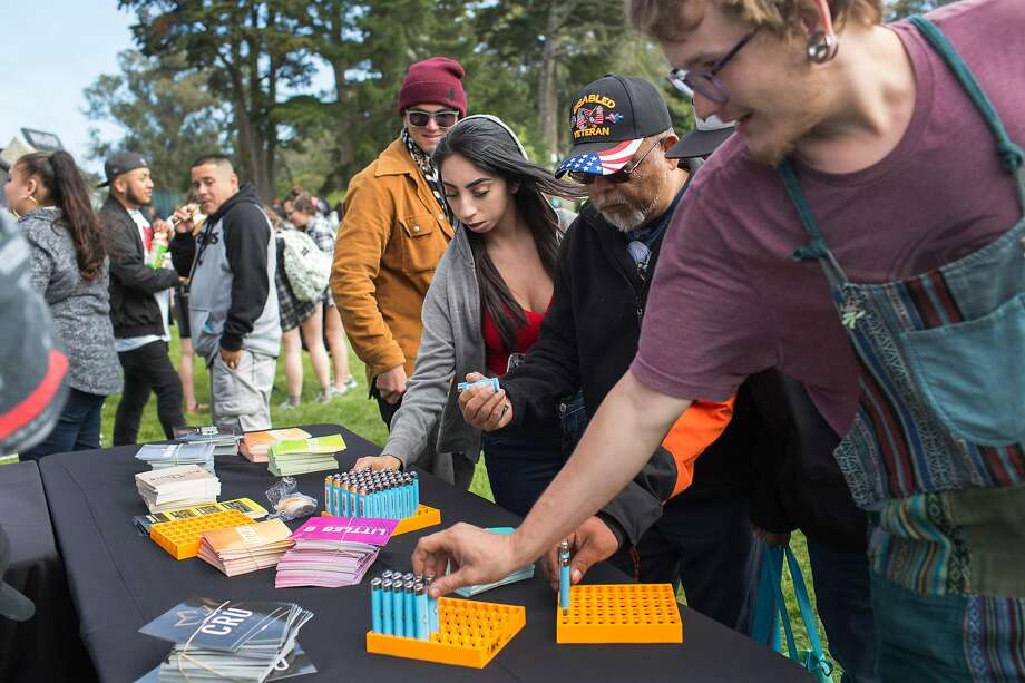 People grab free goods offered by vendors during the annual 420 pot festival at Hippie Hill in Golden Gate Park. Photo: Jana Asenbrennerova / Special To The Chronicle