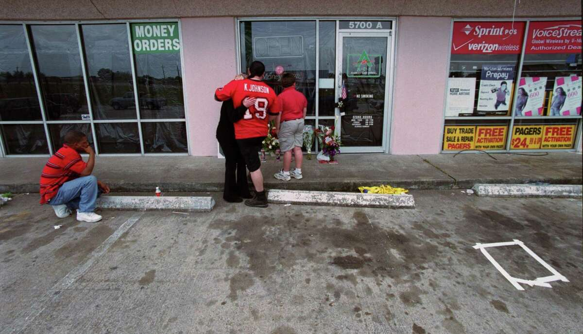 """Brian Gabriel (left), who said of Alfredia Jones, """"She was a great friend,""""and Jerry Daniel and his son, Jerry Lee Daniel III and his fiance, Lora Clark, sister of HPD Officer Charles R. Clark, mourned in front of the ACE Check Cashing facility where Jones and Officer Clark were shot dead."""