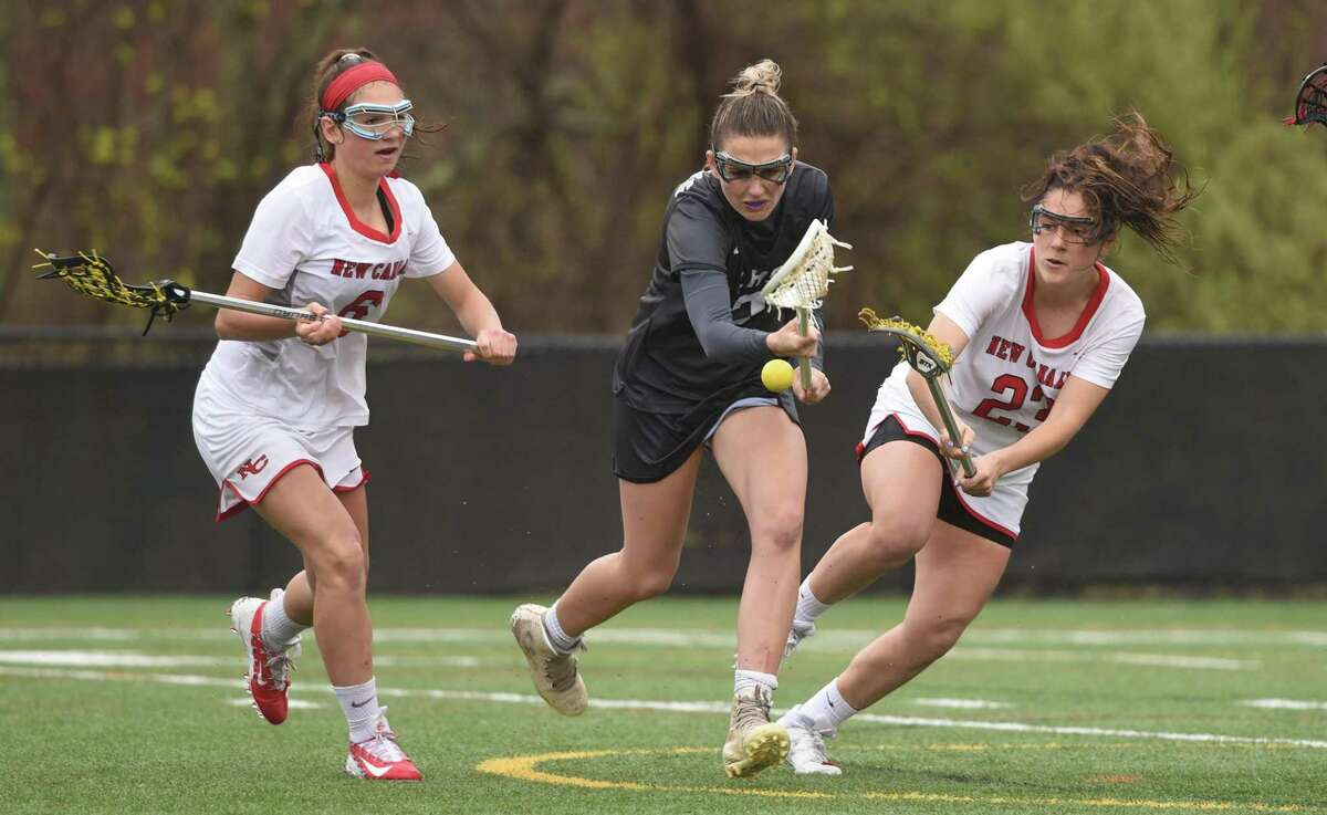 New Canaan's Natalie Lopez (23) knocks the ball away from Henna Brennan (2) of Longmeadow, Mass., as New Canaan's Kaleigh Harden (6) also defends during a girls lacrosse game at Dunning Field on Saturday, April 20.
