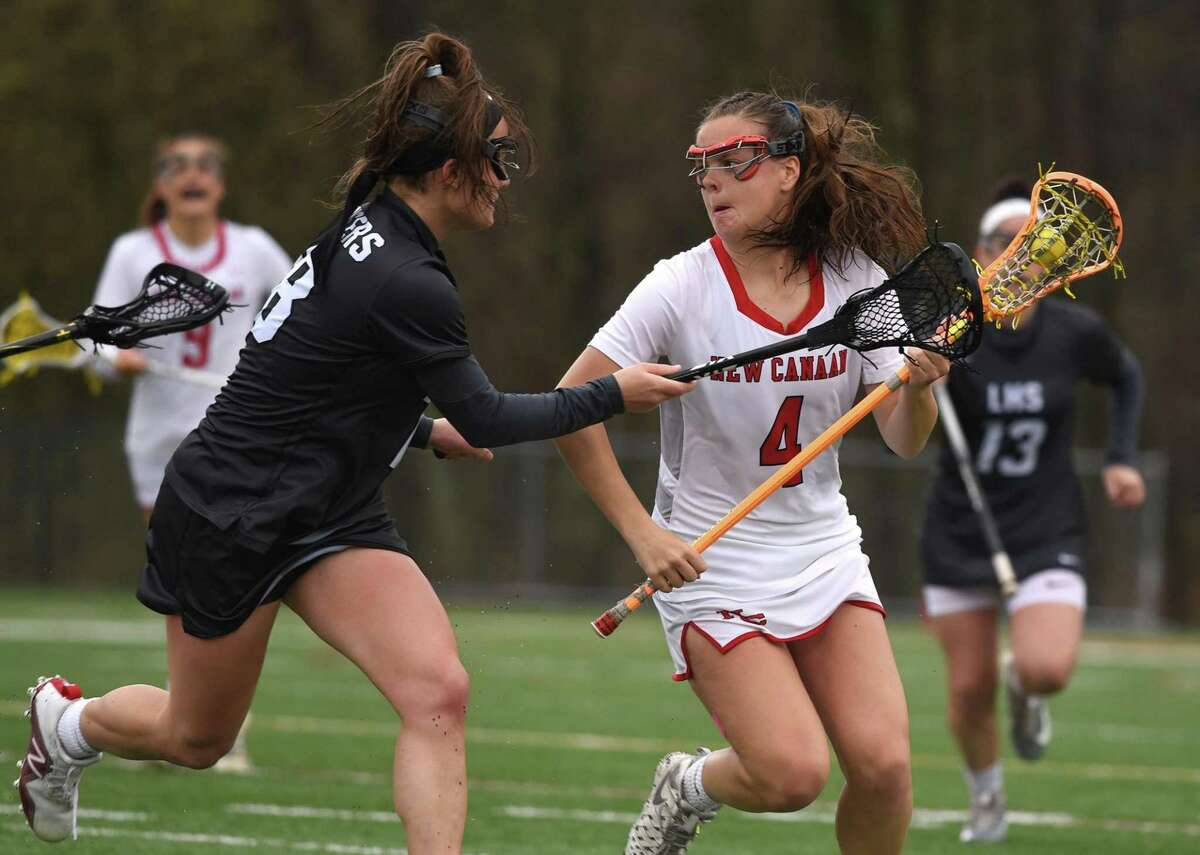 New Canaan's Kendall Patten (4) possesses the ball while Ilana Kofman (18) of Longmeadow, Mass., defends during a girls lacrosse game at Dunning Field on Saturday, April 20.