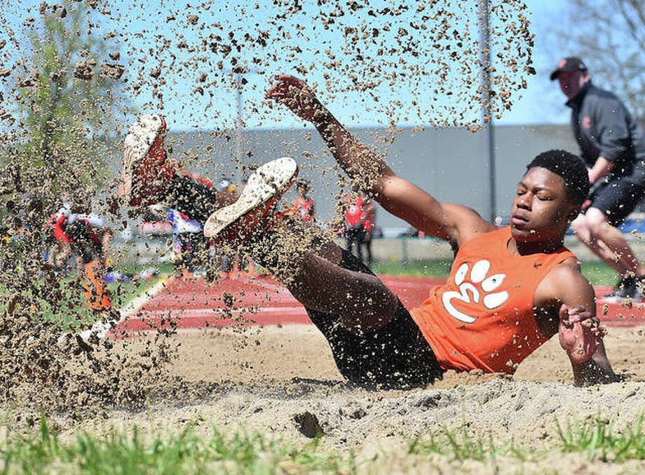 Edwardsville long jumper Kenyon Johnson lands after leaping 22-9 to finish second in the event at the Winston Brown Track and Field Invitational. Photo: Matt Kamp/The Intelligencer