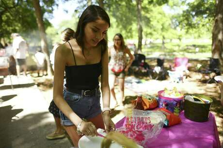 Ashley Peralez loads up on sour cream and chips at Brackenridge Park on Saturday afternoon, April 20, 2019. Many families traditionally camp out at the park on Easter weekend.