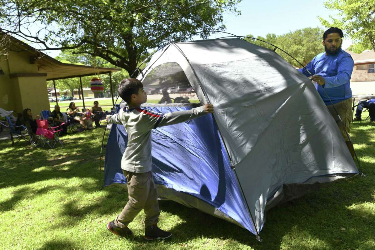 FILE PHOTO --- Saint Gonzales, left, helps his uncle, Jesse Angel, set up a tent at Brackenridge Park on Saturday afternoon, April 20, 2019. Many families traditionally camp out at the park on Easter weekend but the practice has been banned in 2020 and 2021 due to the COVID-19 pandemic.