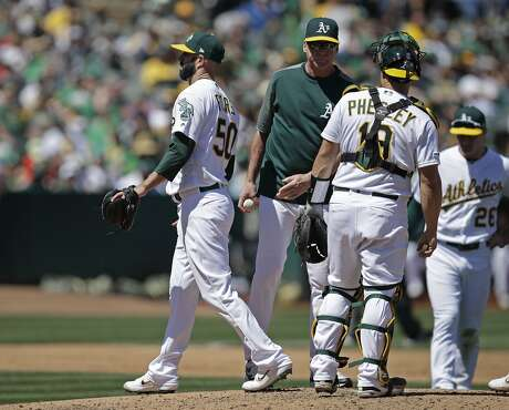 Oakland Athletics pitcher Mike Fiers, left, walks off the mound after being relieved by manager Bob Melvin, second from left, in the fourth inning of a baseball game against the Toronto Blue Jays, Saturday, April 20, 2019, in Oakland, Calif. (AP Photo/Ben Margot)
