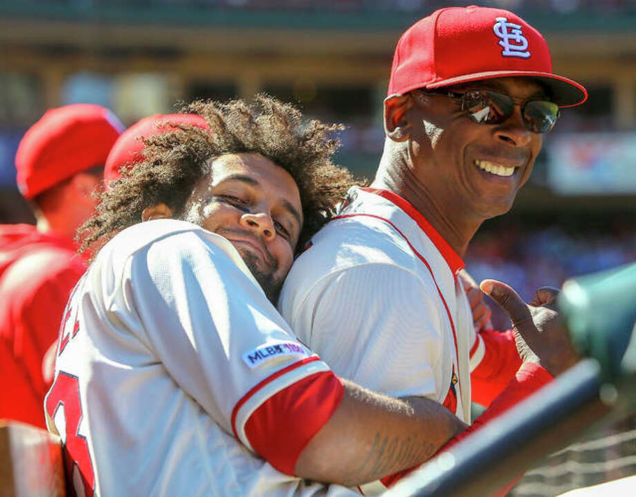 The Cardinals' Jose Martinez (left) hugs assistant coach Willie McGee in the dugout during the seventh inning against the New York Mets on Saturday at Busch Stadium. Photo: Scott Kane / Associated Press