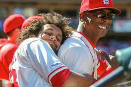 The Cardinals' Jose Martinez (left) hugs assistant coach Willie McGee in the dugout during the seventh inning against the New York Mets on Saturday at Busch Stadium.