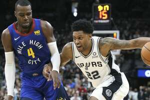 Rudy Gay makes a cut to the lane against Paul Milsap as the Spurs host the Nuggets in game 4 of first round Western Conference playoffs at the Alamodome on April 20, 2019.