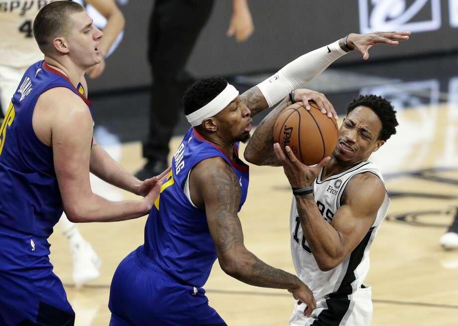 San Antonio Spurs guard DeMar DeRozan (10) is pressured by Denver Nuggets forward Torrey Craig (3) and center Nikola Jokic (15) during the first half of Game 4 of an NBA basketball playoff series in San Antonio, Saturday, April 20, 2019. (AP Photo/Eric Gay) Photo: Eric Gay/Associated Press