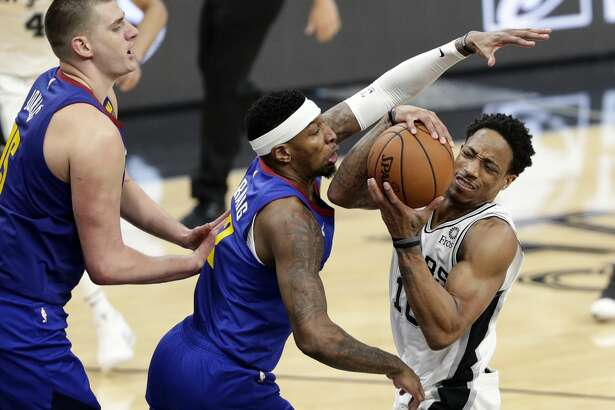 San Antonio Spurs guard DeMar DeRozan (10) is pressured by Denver Nuggets forward Torrey Craig (3) and center Nikola Jokic (15) during the first half of Game 4 of an NBA basketball playoff series in San Antonio, Saturday, April 20, 2019. (AP Photo/Eric Gay)