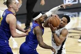 San Antonio Spurs guard DeMar DeRozan (10) is pressured by Denver Nuggets forward Torrey Craig (3) and center Nikola Jokic (15) during the first half of Game 4 of an NBA basketball playoff series in San Antonio, Saturday, April 20, 2019. (AP Photo/Eric Gay)