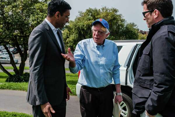 Rep. Ro Khanna, D-Calif., talks to Bernie Sanders before the senator from Vermont takes the stage. In Sanders, Khanna, whose district includes Silicon Valley, found a candidate who shared his diagnosis of the country's most vexing problems: inequality and the failures of unrestrained capitalism.