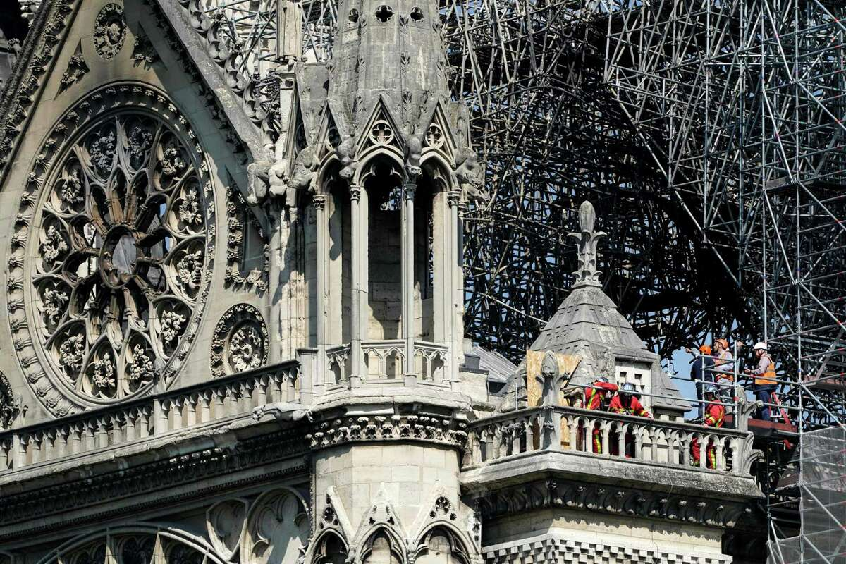 TOPSHOT - Firefighters and technicians work on a balcony of Notre-Dame de Paris Cathedral in Paris on April 19, 2019, four days after a fire devastated the cathedral. - Thousands of Parisians and tourists watched in horror from nearby streets on April 15 as flames engulfed the building and rescuers tried to save as much as they could of the cathedral's treasures built up over centuries. (Photo by Lionel BONAVENTURE / AFP)LIONEL BONAVENTURE/AFP/Getty Images