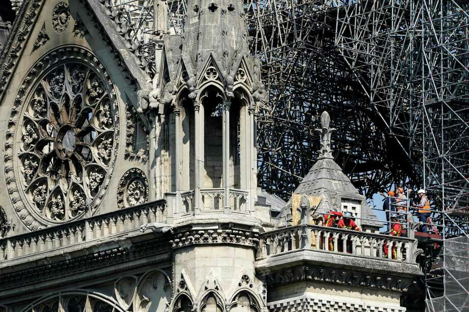 TOPSHOT - Firefighters and technicians work on a balcony of Notre-Dame de Paris Cathedral in Paris on April 19, 2019, four days after a fire devastated the cathedral. - Thousands of Parisians and tourists watched in horror from nearby streets on April 15 as flames engulfed the building and rescuers tried to save as much as they could of the cathedral's treasures built up over centuries. (Photo by Lionel BONAVENTURE / AFP)LIONEL BONAVENTURE/AFP/Getty Images Photo: LIONEL BONAVENTURE / AFP or licensors