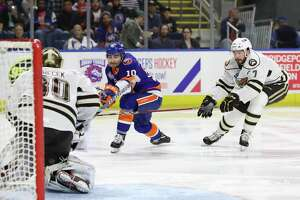Ryan Bourque (10) of the Bridgeport Sound Tigers takes a shot on net while Connor Hobbs (7) of Hershey looks to defend and Vitek Venecek (30) of Hershey looks to make the save during game two of the first round of the AHL Calder Cup Playoffs between the Bridgeport Sound Tigers and the Hershey Bears on April 20, 2019 at Webster Bank Arena in Bridgeport, CT.