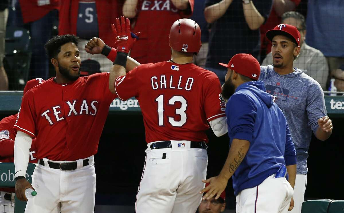 Texas Rangers' Joey Gallo(13) is congratulated by Elvis Andrus, on left, Rougned Odor and Ronald Guzman, on right, after hitting a home run against the Houston Astros during the third inning of a baseball game Saturday, April 20, 2019, in Arlington, Texas. (AP Photo/Mike Stone)
