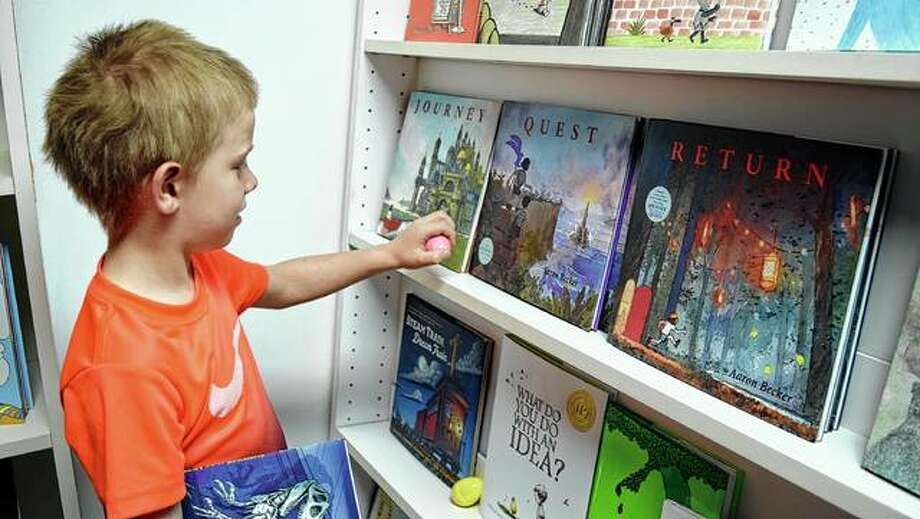 Joesph Vogt, 6, the son of Elizabeth 'Betsy' and Steven Vogt, searches for Easter eggs Saturday at Our Town Books. Photo: Samantha McDaniel-Ogletree | Journal-Courier