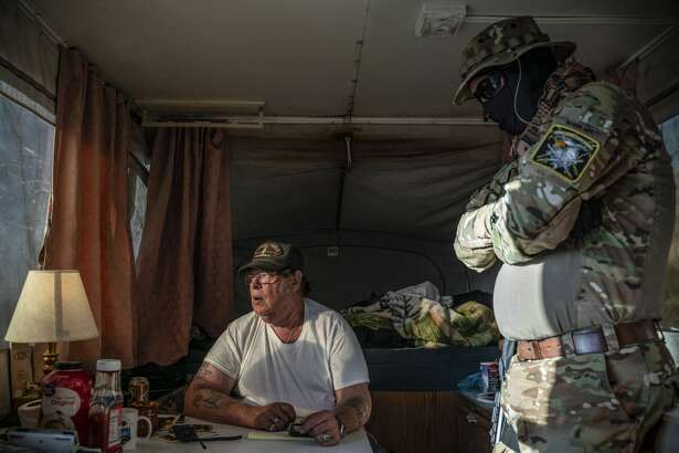 """Striker, the leader of the Constitutional Patriots New Mexico Border Ops Team militia, speaks with Viper (R), who go by aliases to protect their identity, inside the team's camper while discussing logistics on a group chat near the US-Mexico border in Anapra, New Mexico on March 20, 2019. - The militia members say they will patrol the US-Mexico border near Mt. Christo Rey, """"Until the wall is built."""" In recent months, thousands of Central Americans have arrived in Mexico in several caravans in the hope of finding a better life in the United States. US President Donald Trump has branded such migrants a threat to national security, demanding billions of dollars from Congress to build a wall on the southern US border. (Photo by Paul Ratje / AFP) (Photo credit should read PAUL RATJE/AFP/Getty Images)"""