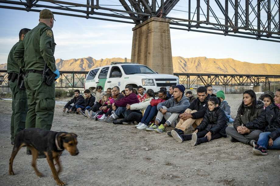 A group of about 30 Brazilian migrants, who had just crossed the border, sit on the ground near US Border Patrol agents, on the property of Jeff Allen, who used to run a brick factory near Mt. Christo Rey on the US-Mexico border in Sunland Park, New Mexico on March 20, 2019. Photo: PAUL RATJE/AFP/Getty Images