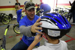 Anadarko Petroleum Corp. volunteer Tim Gregory gives a bike helmet to first-grader Micah Fleetwood at DeZavala Elementary on Oct. 26. Anadarko built bikes for the DeZavala students.