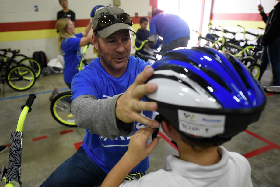 Anadarko Petroleum Corp. volunteer Tim Gregory gives a bike helmet to first-grader Micah Fleetwood at DeZavala Elementary on Oct. 26. Anadarko built bikes for the DeZavala students. Photo: MRT File Photo / © 2018 Midland Reporter-Telegram. All Rights Reserved.
